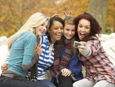 7175740-groupe-de-quatre-filles-adolescentes-se-prendre-en-photo-avec-camera-assis-sur-le-banc-en-automne-pa