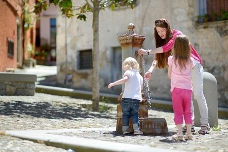 Niños y madre jugando en la fuente